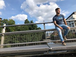 Model wearing Retro75 blue t-shirt leaning on the bridge